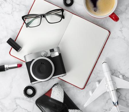 Reizen objecten flatlay op witte houten achtergrond met kopie ruimte. Planner, bril, kopje koffie, camera, oorringen, haarelastiekje, kam en lippenstift aan stijlvolle marmeren tafel. Blogger-concept.
