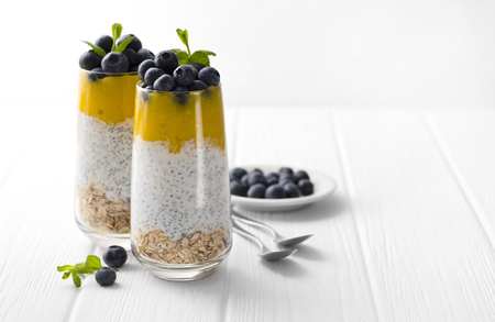 Glass of yogurt with chia seed, blueberries and mango mousse and oatmeal on a white wooden table. Concept of healthy eating, dieting, fitness menu Stock Photo