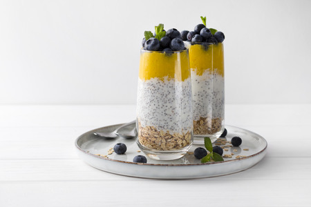 Healthy vanilla chia pudding in a glass with fresh blueberries and mint. Summer breakfast concept