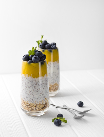 Glass of yogurt with chia seed, blueberries and mango mousse and oatmeal on a white wooden table. Stock Photo
