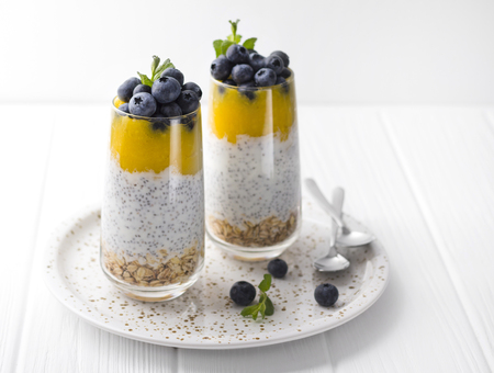Healthy vanilla chia pudding in a glass with fresh blueberries and mint.