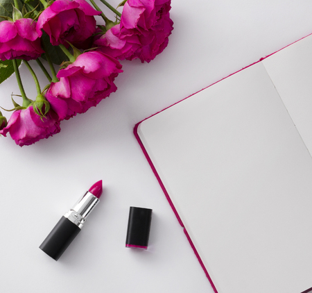 Pink lipstick and roses bouquet with blank notepad on white background. Stockfoto