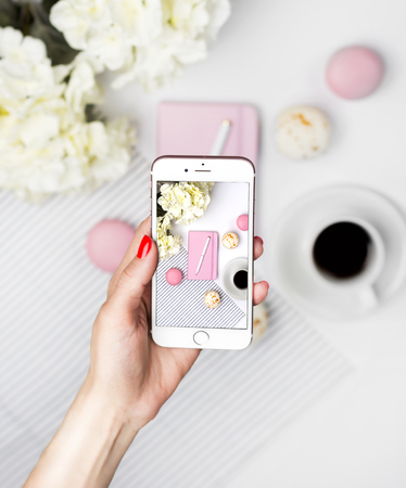 Woman take a picture of workspace on a smartphone. Pink notebook, pen, macaroons, coffee and flowers on white background. Female desktop, office desk, summer concept.