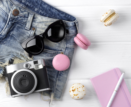 Beach accessories on wooden background. Sorts, macaroons, notebook, camera and sunglasses on wthite.