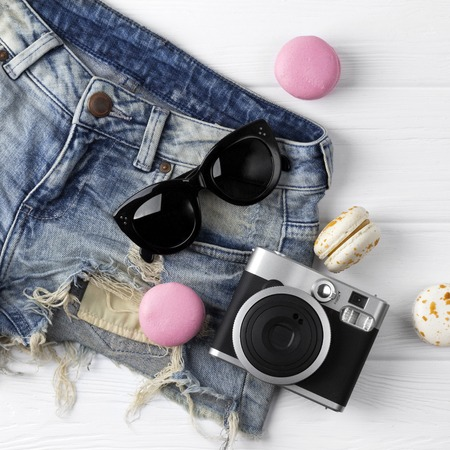 Beach accessories on wooden background. Sorts, macaroons, camera and sunglasses on wthite. 版權商用圖片