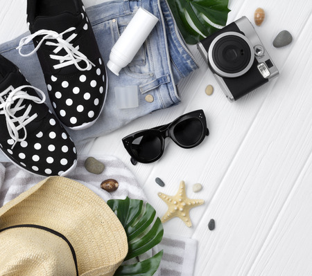 Jeans, sneakers, sunscreen, sunglasses, straw hat, towel, starfish and stones on white with copy space. Beach accessories on wooden background, flat lay.