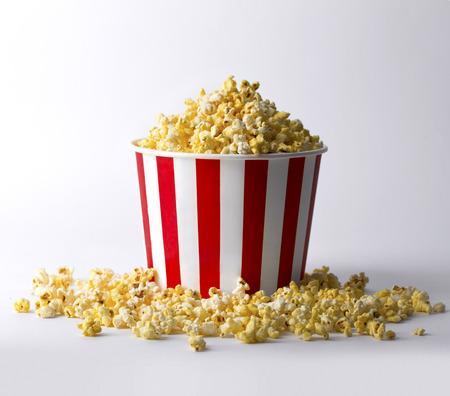 Popcorn in secchio rosso a strisce a fondo bianco. Concetto di passatempo, intrattenimento e cinema.