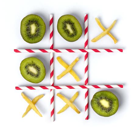 Flat Lay Tic Tac Toe aus Kiwi, Pommes und Strohhalmen. Gesundes vs Junk-Food-Konzept.