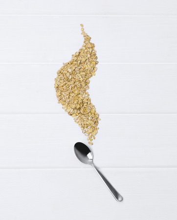 Oat flakes with spoon on white wooden table. Healthy eating concept