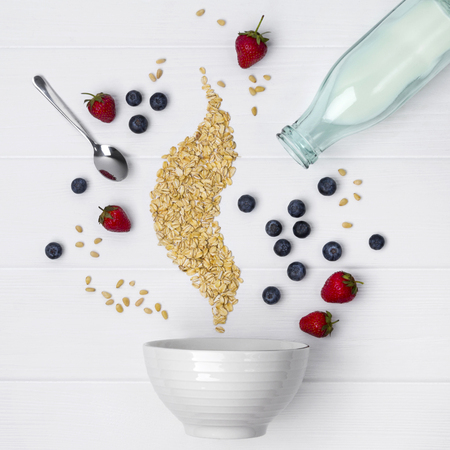 Strawberry, blueberry, pine nuts and oat flakes pours in ceramic bowl for cooking homemade breakfast muesli or granola over white wooden background. Healthy food concept
