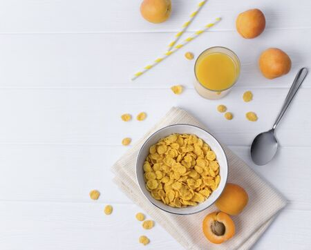Corn Flakes with apricot at the white wooden table. Healthy summer breakfast which consist of different yellow ingredients