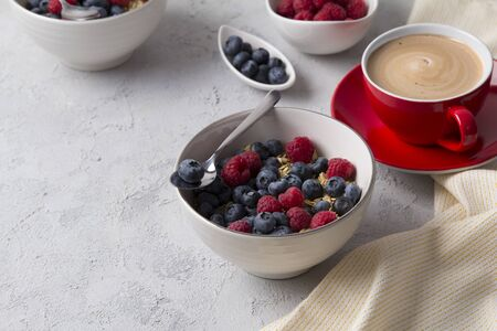 Healthy breakfast with oatmeal, coffee and berries. Oat flakes, blueberries and raspberries on grey concrete background.