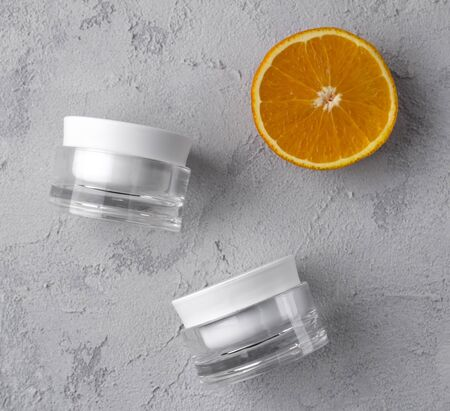 Two cosmetic jar containers with orange. Flat lay blank label for branding mockup. Natural beauty product with vitamin C.