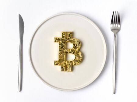 Gold coin bitcoin served on white empty plate with fork and knife