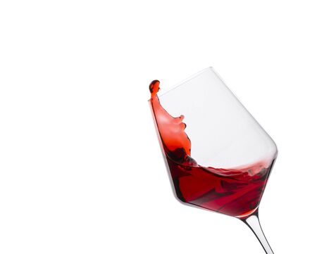 Glass of red wine with splashes on white background. Space for text