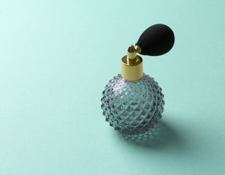 Vintage perfume spray bottle on turquoise background. Top view copy space