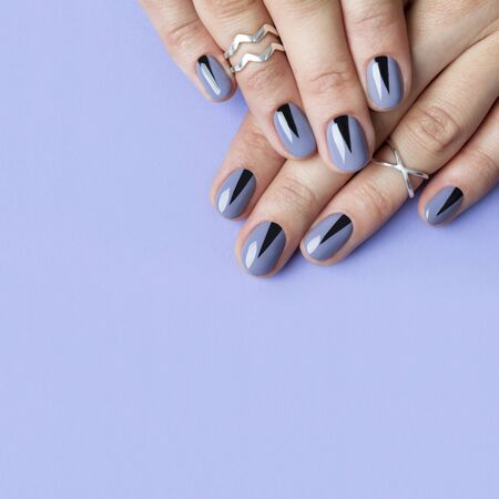 Two female hands with creative minimal manicure at purple background. Salon of nail design concept.