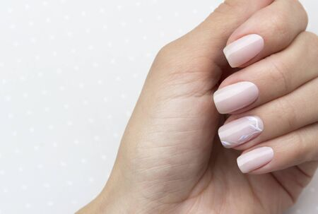 Manos de hermosa mujer arreglada con uñas femeninas sobre el fondo gris claro. Manicura, concepto de salón de belleza de pedicura. Lugar vacío para texto o logotipo.