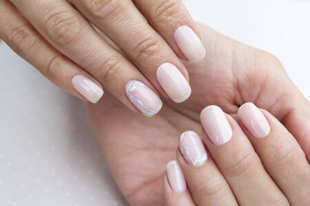 Beautiful groomed woman's hands with feminine nails on the light gray background. Manicure, pedicure beauty salon concept.