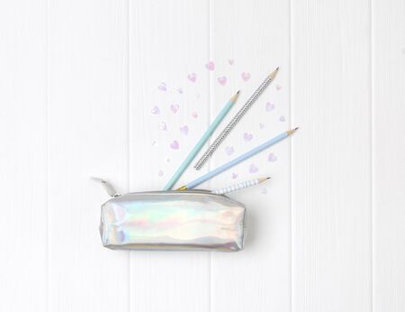 Holographic pencil case with pencils and heart confetti on white wooden background. Back to school concept
