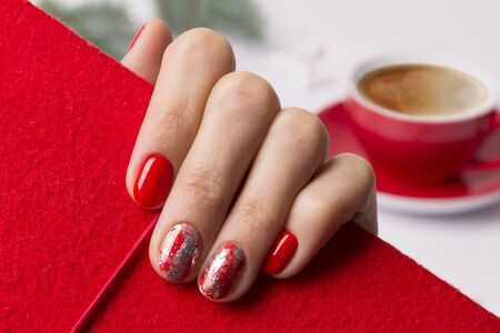 Christmas New Year manicure abstract nail design. Beautiful manicured woman's hand holding notepad at the home office table. Imagens