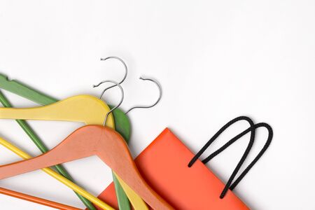 Orange paper shopping bag with colorful hangers over white background. Autumn sale concept. Flat lay copy space Foto de archivo