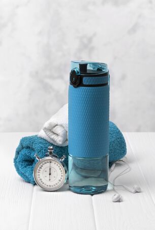 Blue bottle of water, towels, headphones and stopwatch. Sports equipment on white wooden background