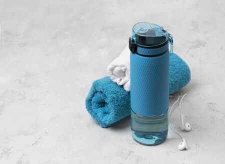 Blue bottle of water and towels. Sports equipment on gray concrete background Stok Fotoğraf