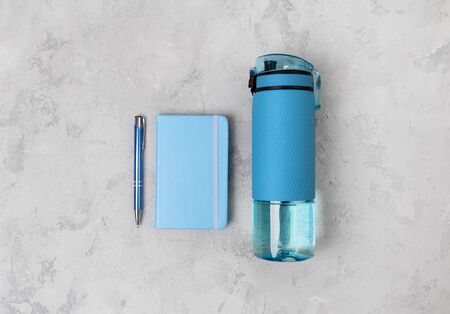 Blue bottle of water and notepad. Sports equipment on gray concrete background Stok Fotoğraf