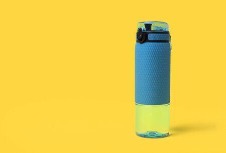 Blue bottle of water. Sport beverage on yellow background Stok Fotoğraf