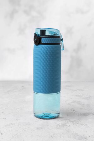 Blue bottle of water. Sport beverage on a gray concrete background.