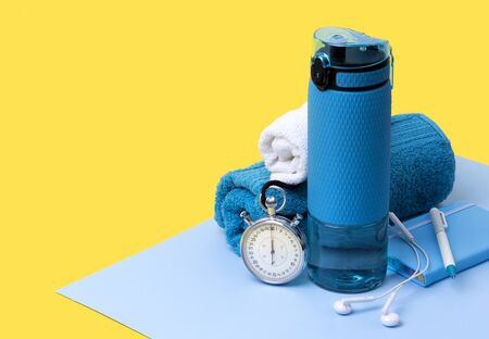 Blue bottle of water, towels, headphones, stopwatch and notepad. Sports equipment on creative background