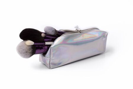 Makeup brushes with holographic cosmetic bag on a white background. Beauty fashion concept concept flat lay top view. Фото со стока