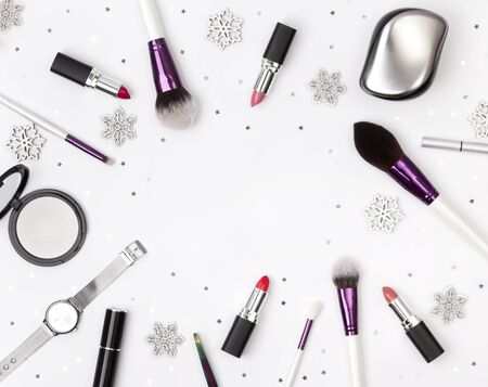 Womens accessories, cosmetics and makeup tools with Christmas decorations on a white background. Winter beauty fashion concept concept flat lay top view.