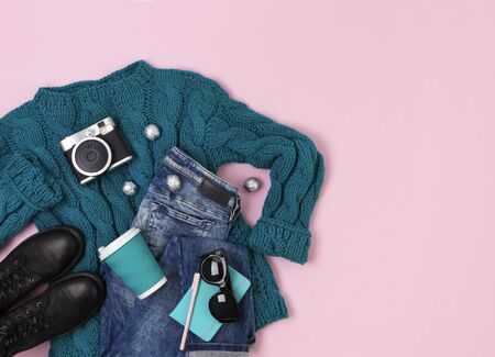 Flat lay top view female casual style look with warm turquoise sweater, jeans, boots and sunglasses