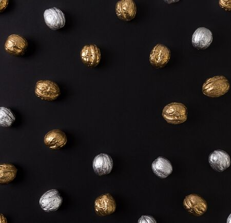 Painted golden and silver walnuts on black background