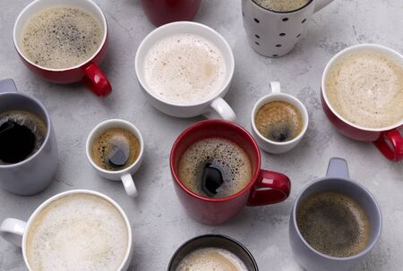 Various coffee in different cups on the concrete gray background. Flat lay top view composition. Good morning coffee break concept.