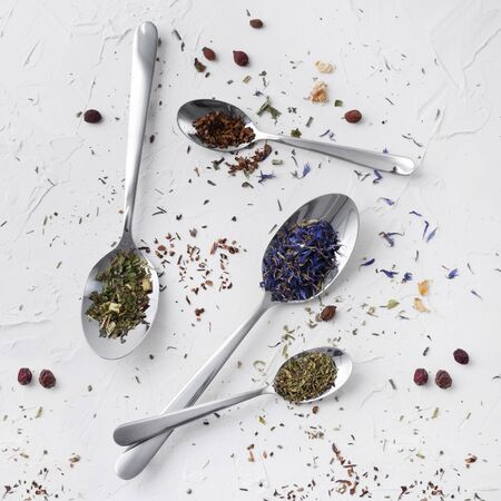Dry tea in silver spoons on white background. Flat lay leaves of red, fruit, herbal tea with spices. Banque d'images - 132113540
