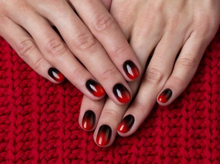 Two female hands with red black ombre gradient nails on knitted fabric