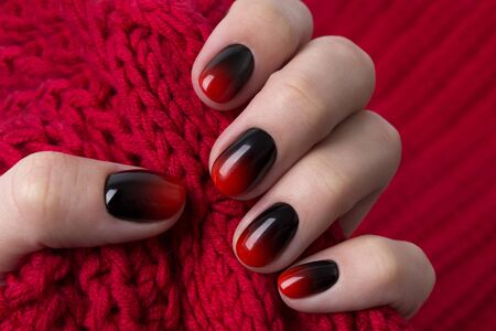 Female hand with red black ombre gradient nails hold wool textile fabric