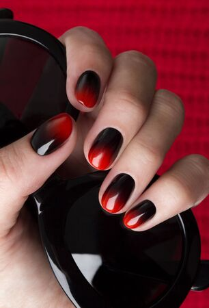 Females hand with red black ombre gradient nails hold sunglasses