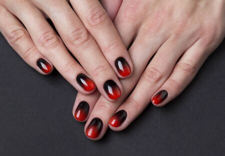 Two female hands with red black ombre gradient nails on dark background 写真素材