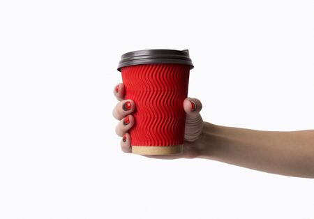 Females hand with red black ombre gradient nails hold paper cup