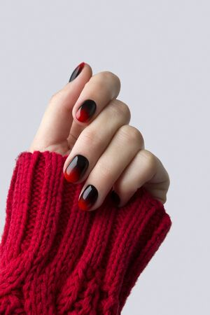 Female hand with red black ombre gradient nails in sweater