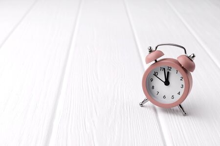 Retro style pink alarm clock on white wooden background shows two minutes to twelve o'clock. Time to wake up template with copy space