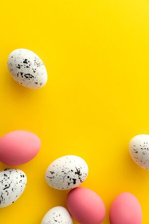 Flat lay top view of white and pink eggs with minimal designs on yellow background. Easter vibrant template greeting card Reklamní fotografie