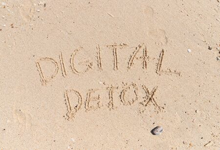 Words digital detox written on yellow sand. Social media gadget internet addiction concept Stock Photo