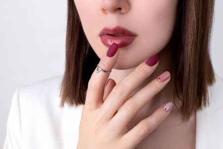 Beautiful woman with a pink manicure in minimal style with jewelry. Summer nail design. Fashion makeup and hands care concept