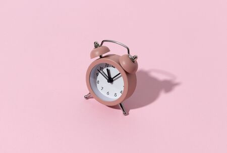 Pink alarm clock on pastel color paper background with copy space. Creative morning time minimal style concept template. 免版税图像