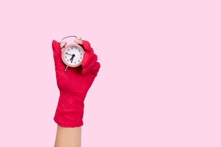Female hand in a rubber glove holding alarm clock on pink background. End of quarantine mock up template with copy space Stock Photo